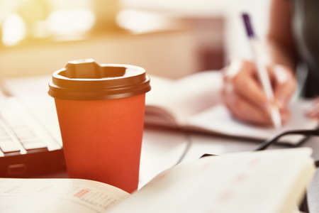 Photo for Remote work concept. Red coffee cup on the workplace. Freelancer work at home - Royalty Free Image