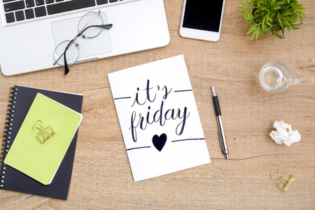 Photo pour Paper with it's friday text calligraphy is in the middle of wood office desk table with supplies. Top view, flat lay. - image libre de droit