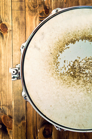 Drums conceptual image. Picture of snare drum lying on wooden background. Retro vintage instagram picture.