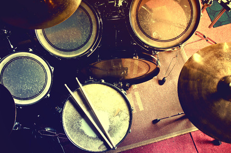 Drums conceptual image. Picture of drums and drumsticks lying on snare drum. Retro vintage instagram picture.