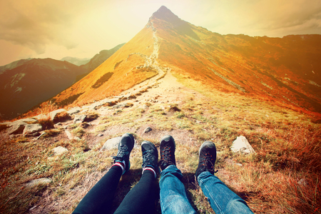 Photo pour Tourism in mountains. A couple of tourists rest on the mountain path. Nature in mountains at autumn. - image libre de droit