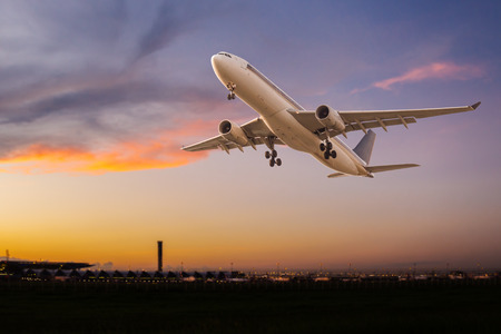 Commercial airplane take off at sunset