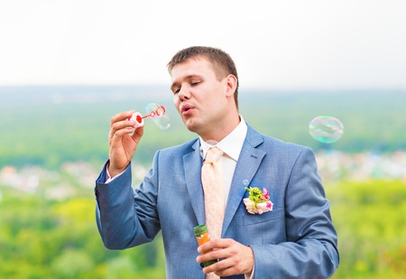 young groom in blue suit blowing bubbles outdoors