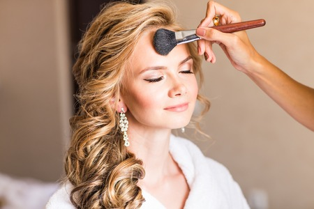 Photo pour Wedding makeup artist making a make up for bride. Beautiful sexy model girl indoors. Beauty blonde woman with curly hair. Female portrait. Bridal morning of a cute lady. Close-up hands near face - image libre de droit