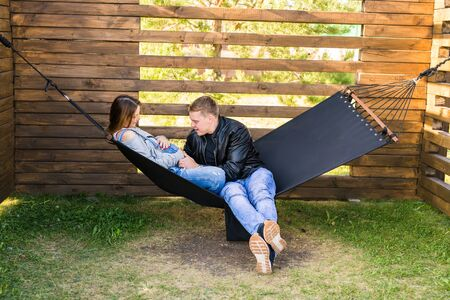 Couple With Pregnant Woman Relaxing On hammock Together