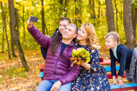 family, childhood, season, technology and people concept - happy family photographing in autumn park.
