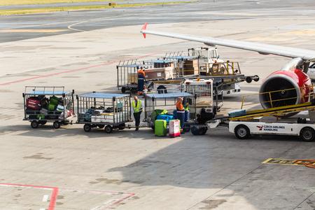 PRAGUE, CZECH REPUBLIC - JUNE 16, 2017: Vaclav Havel Prague International Airport, Ruzyne, Czech Republic. Personnel loading luggage into a plane in an airport