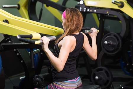 fitness woman execute exercise with exercise machine in gym