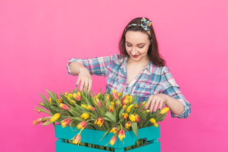 Happy caucasian young woman with box of yellow tulips on pink background