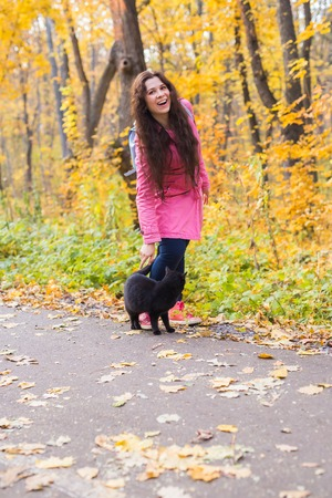 Photo for Fall, pets and people concept - woman and black cat are walking in autumn park - Royalty Free Image