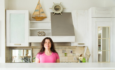 Photo for Housewives, emotions and people concept - Happy young woman in the kitchen at home - Royalty Free Image