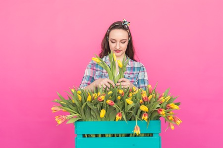 Brunette young woman with bunch of tulips on pink background