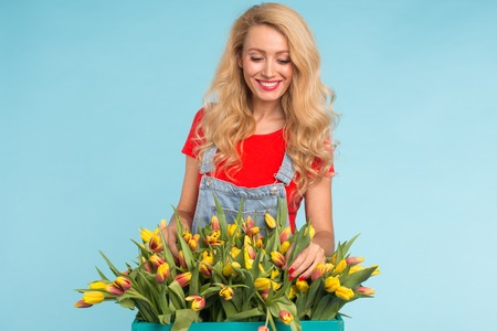 Blonde young woman with bunch of tulips on blue background