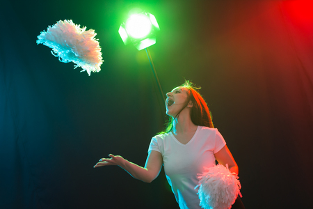 Photo for Dance, sport and people concept - pretty young woman dancing in darkness with pompoms and smiling - Royalty Free Image
