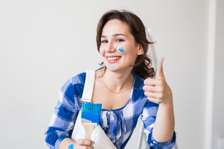 Photo pour Repair, renovation, worker and people concept - Happy young woman paint wall at home, showing us thumbs up - image libre de droit