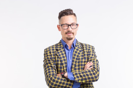 Handsome man in jacket with beard and mustache in glasses having his arms crossed, standing over white background