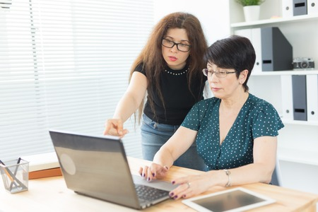 Business people, technology and communication concept - middle-aged woman showing something to another woman on laptop in office
