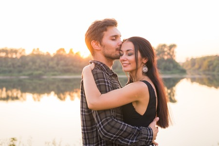 Photo for Relationship, love and nature concept - Close up portrait of attractive woman and handsome man hugging on the background of the lake - Royalty Free Image