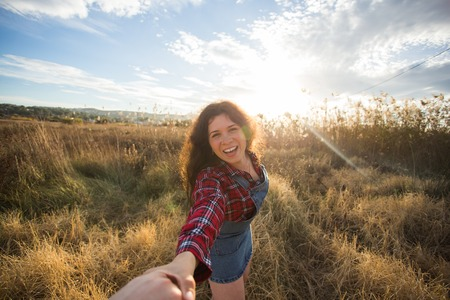 Photo pour Traveling together. Follow me. Young woman holding boyfriends hand walking in the field on sunset - image libre de droit