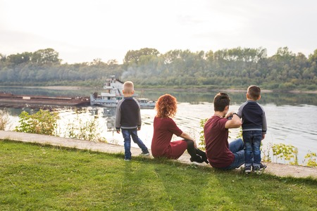 Photo for Parenthood, childhood and nature concept - Family sitting on the green ground and looking at small boat - Royalty Free Image