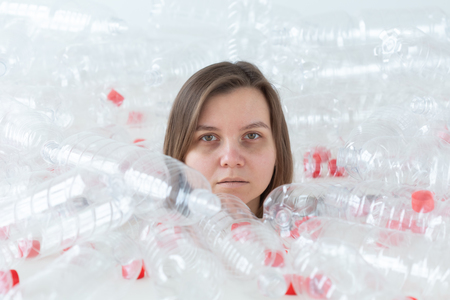 Dehydrated sick woman is lying in a pile of plastic bottles. Environmental pollution problem. Stop nature garbage environment protection concept