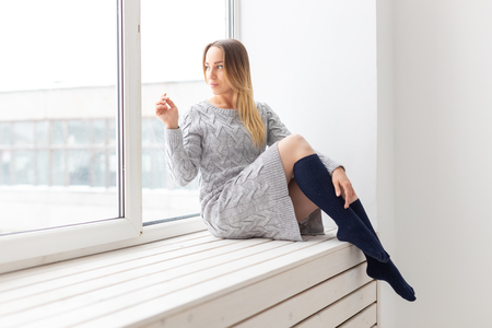 Photo pour People and fashion concept - Gorgeous romantic woman in wool dress sitting on the window sill - image libre de droit