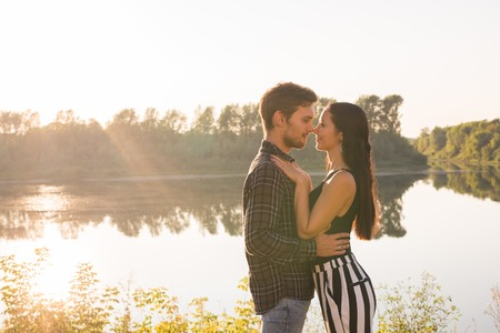 Photo pour People, love and nature concept - Portrait of young beautiful couple embracing each other while standing over nature background - image libre de droit