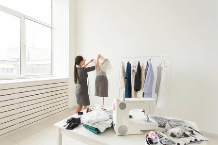 Dressmaker, fashion designer and tailor concept - young fashion designer works in her showroom