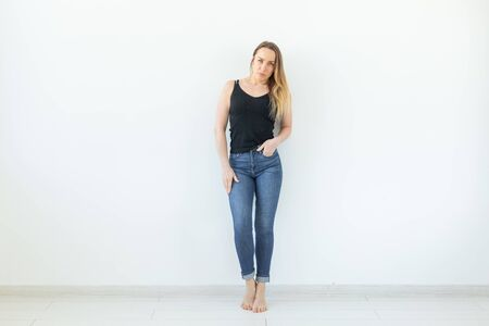 Photo pour Style and people concept - young woman in jeans standing over the white wall and looks like sexy - image libre de droit