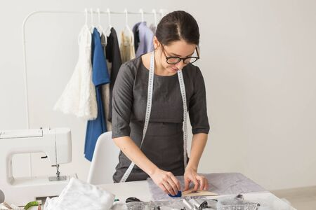 Dressmaker, fashion designer and tailor concept - beautiful young stylist at workplace near rack with clothes