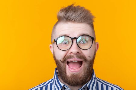 Stylish young hipster man with a mustache and beard joyfully opens his mouth on a yellow background. Concept of surprise and celebration. Copyspace.