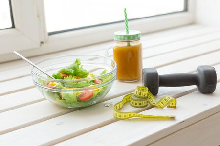 Foto de Vegetable salad and fruit smoothies and dumbbell lie on a white windowsill. Concept of healthy lifestyle physical activity and proper nutrition. - Imagen libre de derechos