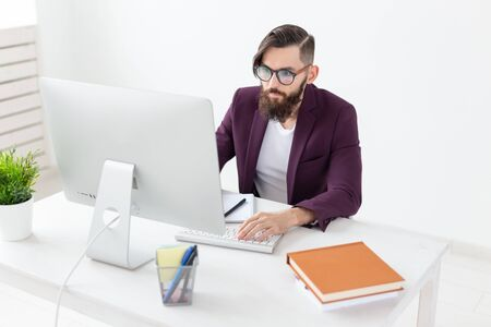 Foto de People and technology concept - Attractive man with beard working on at the computer - Imagen libre de derechos