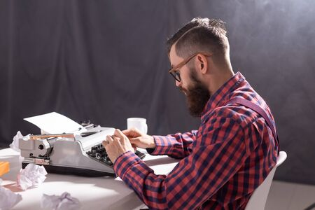 Vintage, writer and hipster concept - young stylish writer working on typewriter