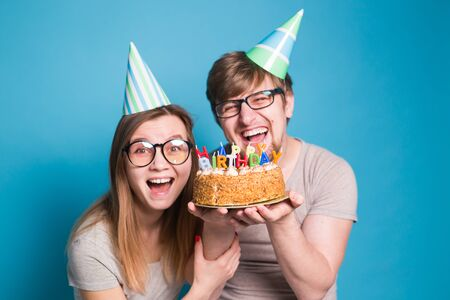Foto de Cheerful young couple charming guy and cute girl in paper hats make foolish face and hold in their hands a birthday cake standing on a blue background. - Imagen libre de derechos