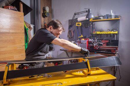 Photo for A man repairman in workshop ski service repairing the ski - Royalty Free Image