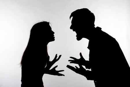 Foto de Relationship difficulties, conflict and abuse concept - man and woman face to face screaming shouting each other dispute silhouette isolated on white background - Imagen libre de derechos