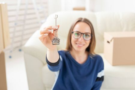 Photo pour Moving, real estate and apartment purchase concept - Happy single woman apartment owner or renter showing keys and looking at you - image libre de droit