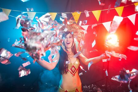 Photo pour Cabaret, dancer and holidays concept - Cute young girl in bright colorful carnival costume on dark background - image libre de droit