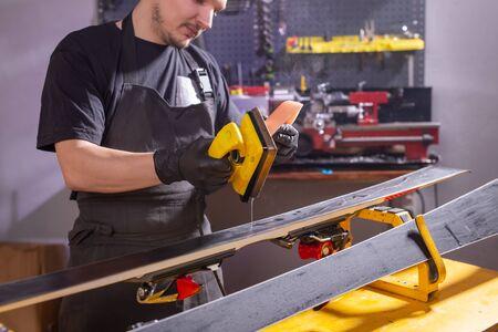 Photo pour Repair, people concept - mechanic, man is rubbing a ski - image libre de droit