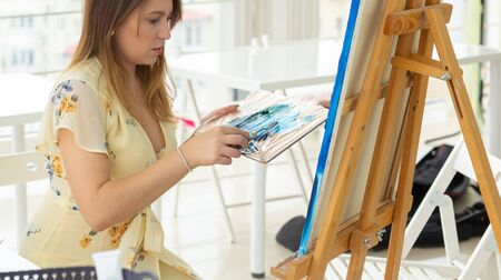 Art school, creativity and leisure concept - student girl or young woman artist with easel, palette and paint brush painting picture at studio, close-up