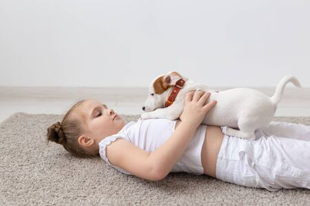 Photo pour people, children and pets concept - little kid girl lying on the floor with cute puppy. - image libre de droit