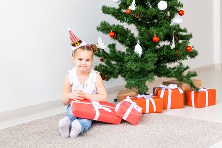 Photo for Kid opening Xmas presents. Child under Christmas tree with gift boxes. - Royalty Free Image