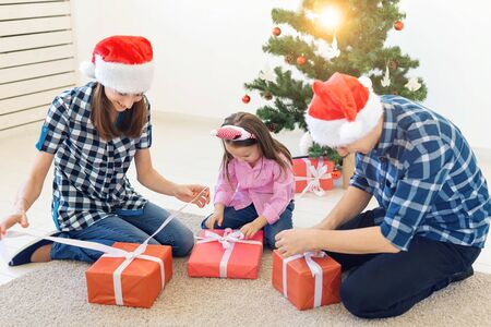 Photo for Holidays and presents concept - Portrait of a happy family opening gifts at Christmas time - Royalty Free Image