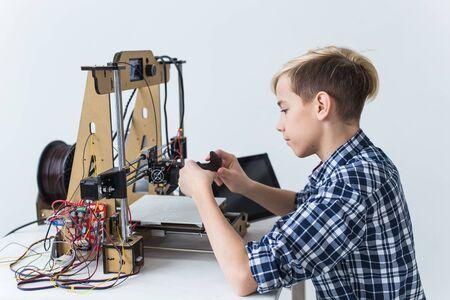 Photo pour Education, children, technology concept - teen boy is printing on 3d printer. - image libre de droit