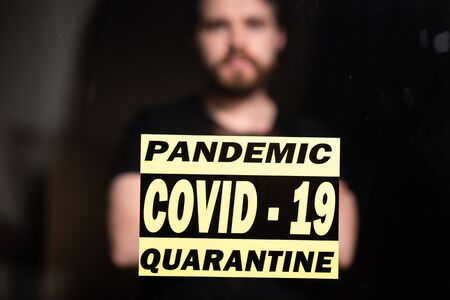 Coronavirus, quarantine, covid-19 and pandemic concept. Sad and sick man of corona virus looking through the window. Stay at home.