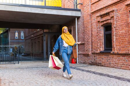Photo pour Sale and buying concept - Happy arab muslim girl with shopping bags after mall - image libre de droit