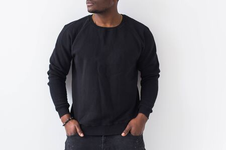 Photo pour Close-up of n African American man posing in black sweatshirt on a white background. Youth street fashion photo with afro hairstyle. - image libre de droit