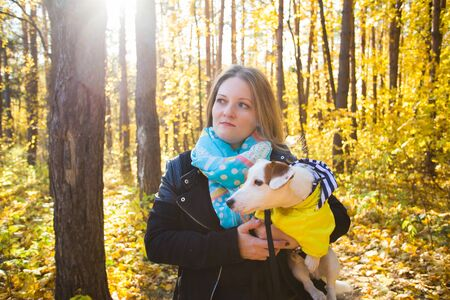 Photo for Woman with a dog jack russell terrier. Friendship and pet concept. Small dog walking in the autumn park. - Royalty Free Image
