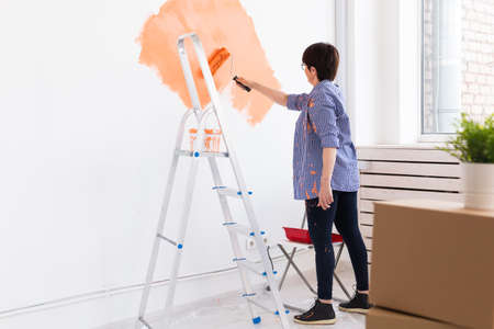 Photo pour Happy middle-aged woman painting wall in her new apartment. Renovation, redecoration and repair concept. - image libre de droit